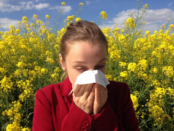 A woman sneezing into a tissue | Is Tofu Healthy? 21 Benefits and Disadvantages - It Can Cause An Allergy Flare