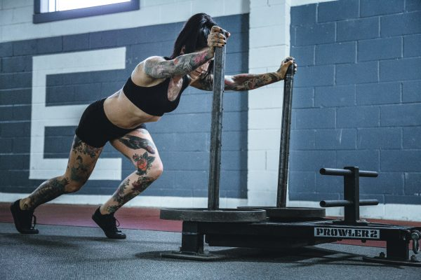 A woman pushing a weight sled in a gym | Is Tofu Healthy? 21 Benefits and Disadvantages - It Helps Build Muscle