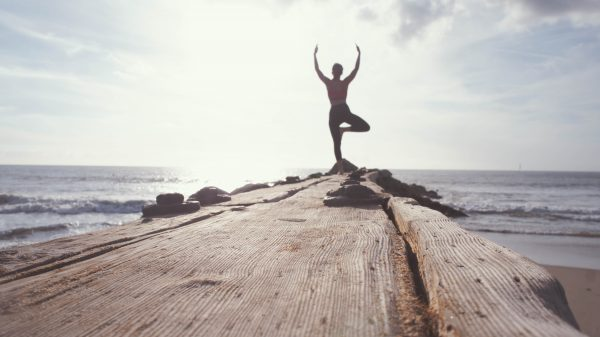 A woman doing a yoga pose on a pier by the ocean | Is Tofu Healthy? 21 Benefits and Disadvantages - It Contains Heart Health Omega-3s