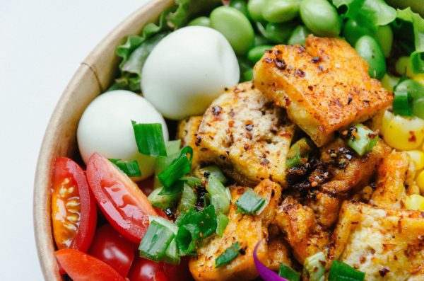 A bowl of tofu, eggs, tomatoes, edamame, lettuce, and green onions | The Best Vitamin B12 Foods for Vegetarians and Vegans