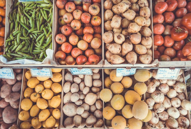 Bins at a farmer's market full of potatoes, fruits, and other vegetables | Macronutrients vs. Micronutrients: The Complete Guide